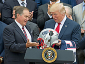 New England Patriots head coach Bill Belichick, left, presents a team helmet to United States President Donald J. Trump, right, after making remarks during the ceremony welcoming the Super Bowl Champions to the South Lawn of White House in Washington, DC on Wednesday, April 19, 2917.  <br /> Credit: Ron Sachs / CNP<br /> (RESTRICTION: NO New York or New Jersey Newspapers or newspapers within a 75 mile radius of New York City)