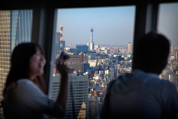 Tokyo, July 27 2010 - People enjoying the view from the Tokyo tower, second highest building in Japan. In the backgroung, the newly built Tokyo Sky Tree, tallest artificial structure in Japan.