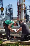 SCHIEDAM - Langs de Wiltonhaven in Schiedam werken medewerkers van dak- en gevelspecialist Erdo aan de opbouw van gevelpanelen voor een produktiehal van Huisman. De door ASK Romein te bouwen assemblagehal die bedoeld is om de offshore constructies van Huisman binnenshuis te monteren, zal volgens Erdo met 66 meter hoogte de hoogste productiehal van Nederland worden. Vanwege de beperkte ruimte op de bouwplaats, worden de panelen aan de overzijde van de haven in elkaar gezet, om later op locatie te worden ingelezen en gemonteerd..COPYRIGHT TON BORSBOOM.COPYRIGHT TON BORSBOOM