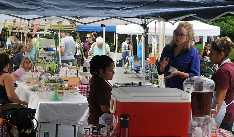 Ayla Rector, the Market Manager (at right) visiting one of the booths at the weekly Saugerties' Farmer's Market in Saugerties, NY on Saturday, July 2, 2016. Photo by Jim Peppler. Copyright Jim Peppler 2016.