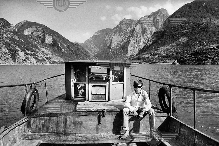 A youth listens to his radio on one of the now numerous motorised boats used for ferrying people and goats across the Drin reservoirs.