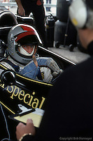 ANDERSTORP - JUNE 13: Mario Andretti, sitting in his Lotus 77 R1/Ford Cosworth DFV, gestures with his hand as he speaks with Colin Chapman during practice for the Swedish Grand Prix on June 13, 1976, at Scandinavian Raceway near Anderstorp, Sweden.
