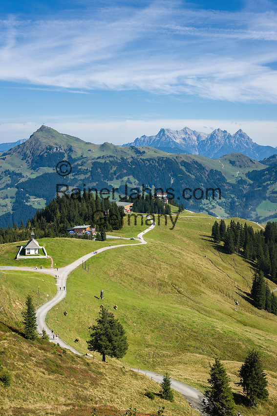 Austria, Tyrol, above Kitzbuhel: view from 'Ehrenbachhoehe' mountain towards Hahnenkamm mountain with St. Bernhard chapel (also Hahnenkamm-Chapel) and Hahnenkamm cable car station, at background Loferer Steinberge mountains | Oesterreich, Tirol, oberhalb Kitzbuehel: Blick von der Ehrenbachhoehe zum Hahnenkamm mit St. Bernhard Kapelle (auch Hahnenkamm-Kapelle) und der Hahnenkammbahn Hochkitzbuehel, im Hintergrund die Loferer Steinberge