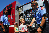 Patrick Hayes and his sister, Sophia, talk with Madison firefighters Steve Dahlgren (right) and Jason Suttle (left) at emergency response demonstrations at All-Star Sunday at Warner Park.
