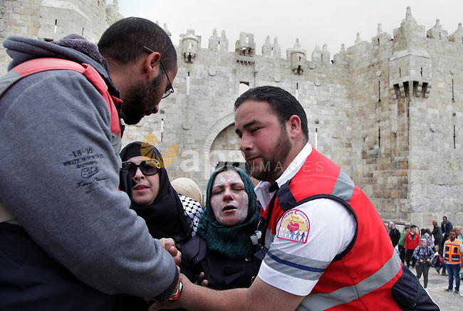 A Palestinian medic treats a woman after Israeli border police officers sprayed pepper spray during a demonstration marking the Land Day in Jerusalem's old city, Sunday, March 30, 2014. The Land Day commemorates the Israeli government expropriation of thousands of dunams of land from Palestinians in 1976. Photo by Saeed Qaq