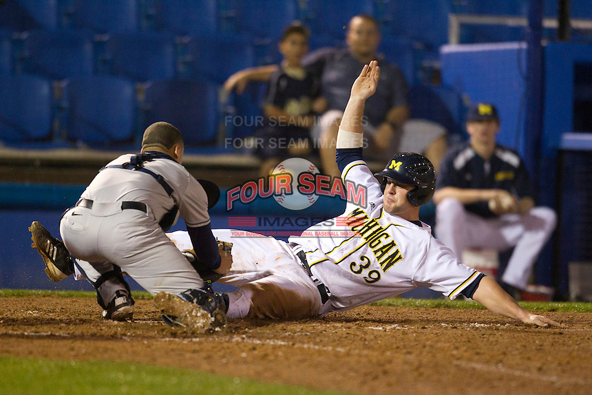 Michigan Wolverines first baseman Brett Winger #39 slides into home as Elvin Soto #7 attempts to apply the tag during a game against the Pittsburgh Panthers at the Big Ten/Big East Challenge at Florida Auto Exchange Stadium on February 17, 2012 in Dunedin, Florida.  (Mike Janes/Four Seam Images)