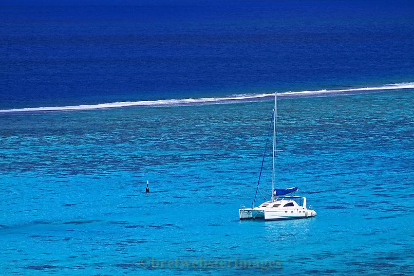 Calm waters inside the atoll in Tahiti give a serene scene with a catamaran.
