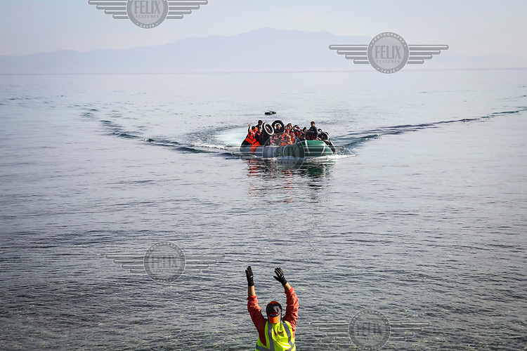A volunteer signals to a dingy, carrying refugees and migrants, as it approaches the shore.