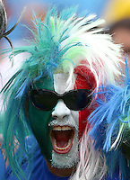 An Italy fan with painted face and wig cheers his side on