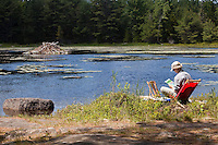 A woman paints a lake and a beaver house by the side of a lake in Acadia National Park on Mount Desert Island in Maine Wednesday June 19, 2013. Created as Lafayette National Park in 1919 and renamed Acadia in 1929, the park includes mountains, an ocean shoreline, woodlands, and lakes.