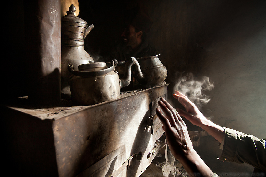 A Kyrgyz dries his hands on the stove - a left over from the short Russians occupation of the Pamir, in the early 1980's...Trekking up the Wakhan frozen river, the only way up to reach the high altitude Little Pamir plateau, home of the Afghan Kyrgyz community.