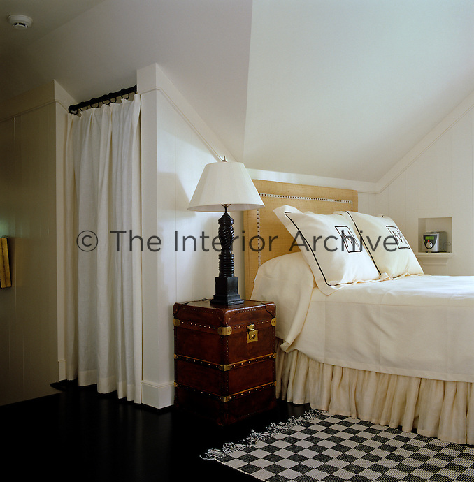 Curtains are used as a door to the under-eaves storage space in this compact yet elegant bedroom