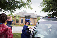Stella Greenhill (from center left) holds hands with Mosely Greenhill, 13, Friday, May 15, 2020 during a graduation ceremony at The New School in Fayetteville. The New School celebrated its first graduation in a hybrid virtual/in-person ceremony. <br /> <br /> The senior class consisted of 11 students. The ceremony was conducted outdoors where graduates and their families, the only guests in attendance outside of essential faculty and staff, were restricted to spaces within safe social distances to view pre-recorded programming and to allow graduates to accept their diplomas one at a time. Check out nwaonline.com/200516Daily/ for today's photo gallery. <br /> (NWA Democrat-Gazette/Charlie Kaijo)