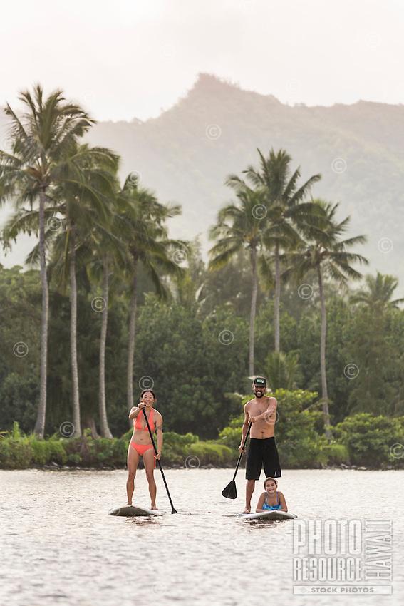 A family learns to standup paddle on Wailua River, Kaua'i.