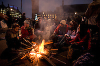 Protestors sit around a fire to keep warm on Parliament Square during a student demonstration in Westminster, central London on the day the government passed a bill to increase university tuition fees.