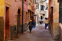"View from behind of a woman walking in a narow street of the old city of the Portuguese Fortified city of Mazagan, El Jadida, Morocco. El Jadida, previously known as Mazagan (Portuguese: Mazag""o), was seized in 1502 by the Portuguese, and they controlled this city until 1769.  Picture by Manuel Cohen"