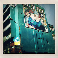 A huge photograph of Afghan President Hamid Karzai being hugged by a young boy adorns the side of a drab building in Kabul.