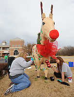 NWA Media/ANDY SHUPE - Kimberly George, left, and her daughter, Ryen Elliott, 17, paint Ole' Paint Jr., a fiberglas horse outside George's business, Northwest Arkansas Florist, Sunday, Dec. 7, 2014, in Bentonville. The 15-year-old horse, and another 38-year-old horse in Fayetteville named Ole' Paint, normally is decorated each month by nonprofits to advertise upcoming events. Despite the horses' schedules being booked for the next two years, there was no takers for December so George and her employees decided to paint it themselves for the first time.