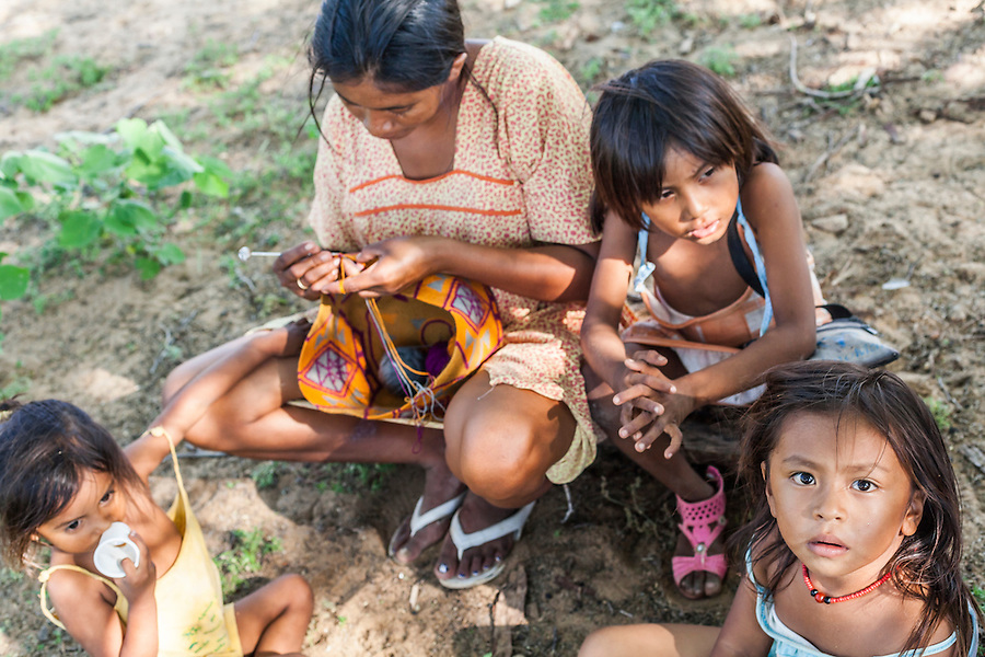"Young Wayuu woman and her children sitting outside while she knits in a ""rancheria"", or traditional Wayuu settlement in La Guajira, Colombia.   Knitting, crocheting and weaving are fundamental to the social and economic lives of Wayuu women in La Guajira, Colombia."