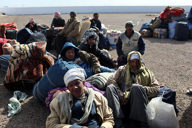 A group of men waited with their belongings at the Tunisia-Libya border near Ben Guerdane, Tunisia, Friday, Feb. 26, 2011. Thousands of foreign workers continued their exodus across the border into Tunisia, fleeing violence sparked by an uprising against Col Muammar Qaddafi. The refugees, primarily Egyptians, had to wait at the border or at an improvised camp nearby until a bus could take them to the airport in Tunis.