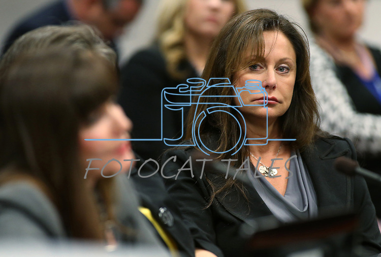 Bridgette Denison listens as Jayann Sepich testifies on a bill that would require collection of a DNA sample from people arrested on felony charges, during a hearing at the Legislative Building in Carson City, Nev., on Thursday, May 9, 2013. The bill, also known as Brianna's Law, is named after Denison's 19-year-old daughter who was murdered in Reno in 2008. (AP Photo/Cathleen Allison)