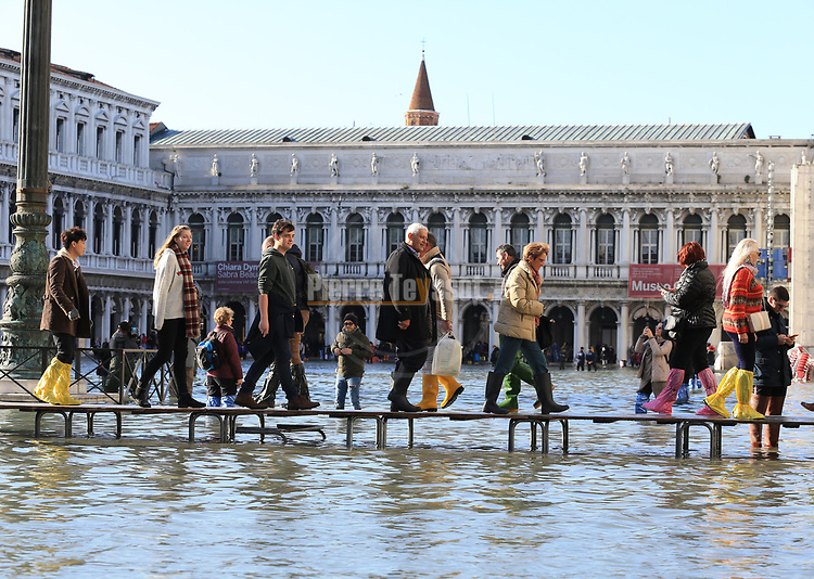 Venice underwater as exceptional tide sweeps through canal city.<br /> <br /> People walk on a footbridge across the flooded St. Mark's Square by St. Mark's Basilica on November 14, 2019 in Venice. Much of Venice was left under water after the highest tide in 50 years ripped through the historic Italian city, beaching gondolas, trashing hotels and sending tourists fleeing through rapidly rising waters.