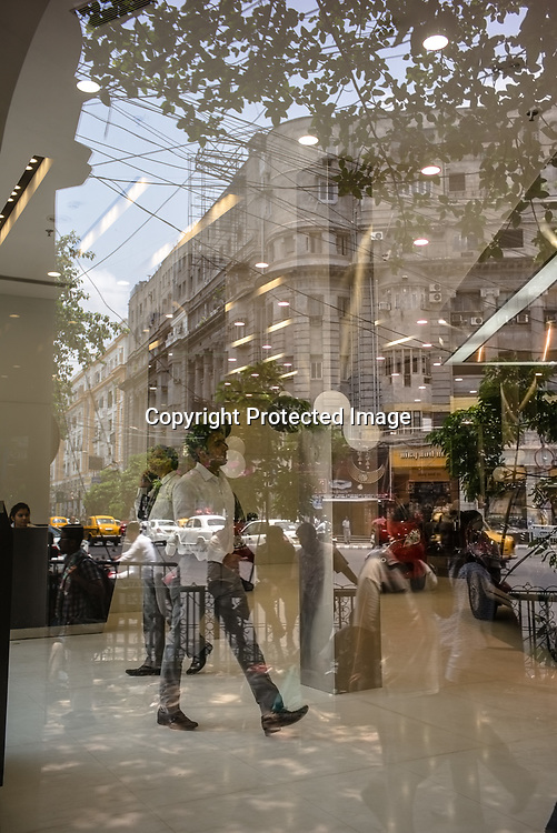 The newly renovated British Colonial buildings on Park Street are reflected on the shop window of the Maruti Suzuki Car showroom on Park Street in Kolkata, West Bengal  on Friday, May 26, 2017. Photographer: Sanjit Das