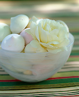 A close up of a bowl of pink and white meringues topped with a creamy rose