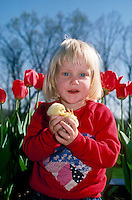 Blonde girl holding chick in front of blooming tulips