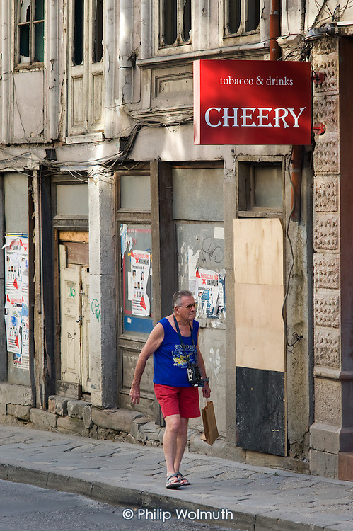 A tourist walks past a closed business in Veliko Tarnovo.  Although a popular tourist destination, the town has suffered as a result of the financial crisis.