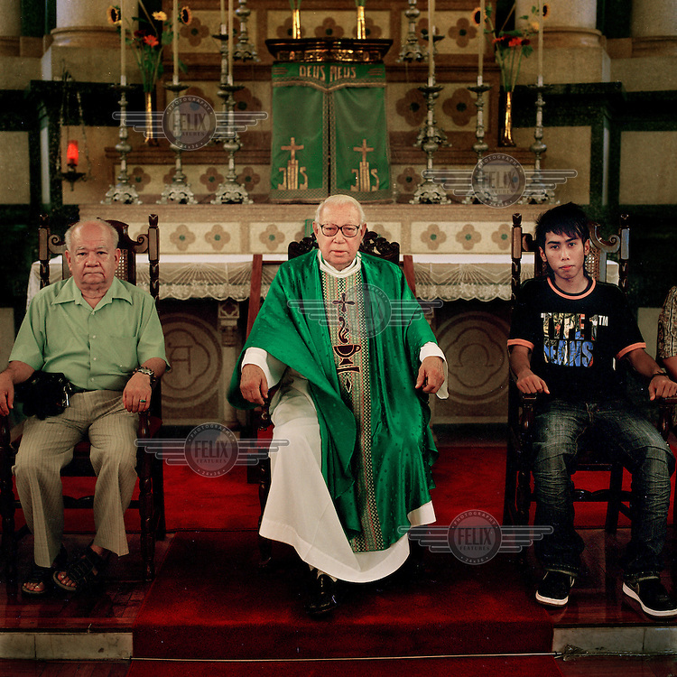 85 year old missionary Father Lancelot (centre)  sits in front of an alter in church during Sunday worship.