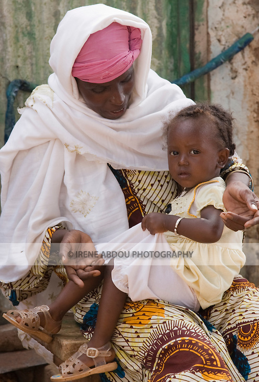Haoua Pendooru, a Fulani woman, sits with her daughter in her lap at her home in Ouagadougou, Burkina Faso.