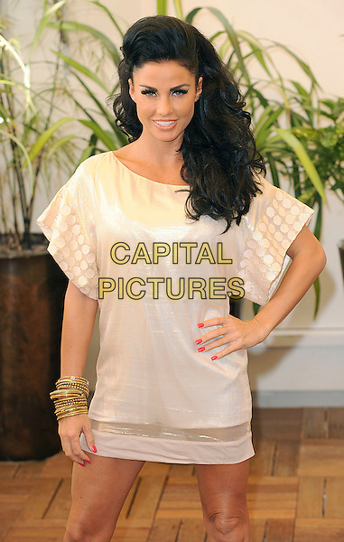 """KATIE PRICE aka JORDAN.At a photocall for her new ITV 2 programme """"What Katie Did Next"""", The Sanctum Soho Hotel, Soho, London, England, August 25th 2009..half length cream white dress shiny polka dot patterned print gold bracelets  hand on hip hair quiff .CAP/BEL.©Tom Belcher/Capital Pictures."""