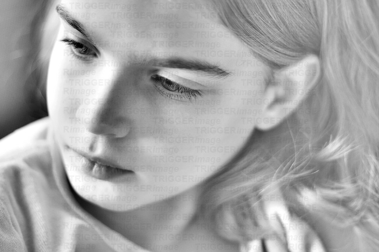 Close up of a young girls face looking thoughtful with blonde hair in b/w
