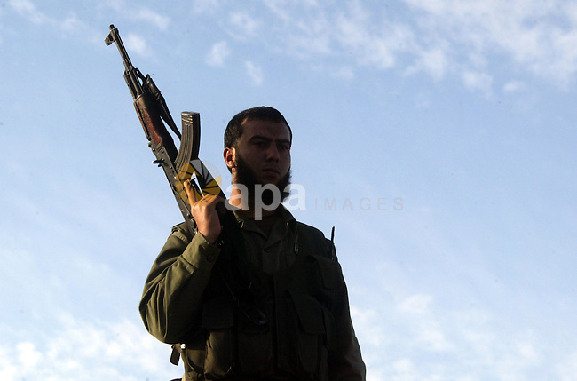 A member of Hamas security forces stands guard of the Palestinian side of divided Rafah, in front of an Egyptian watchtower on the border with the southern Gaza Strip on December 21, 2009, while a few hundred Hamas supporters hold a rally in Rafah to protest Egypt's construction of an underground wall to stem smuggling to the besieged Gaza Strip territory Egypt has only implicitly confirmed the construction of the underground wall, which was first reported by Israeli media, saying it is aimed at protecting its territory from security threats. Photo by Abed Rahim Khatib