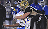 Joe Valenti #30 of Wantagh, right, puts pressure on Roosevelt quarterback Stephan Vailes #17 during the Nassau County varsity football Conference III final at Hofstra University on Friday, Nov. 18, 2016. Wantagh won by a score of 13-0.