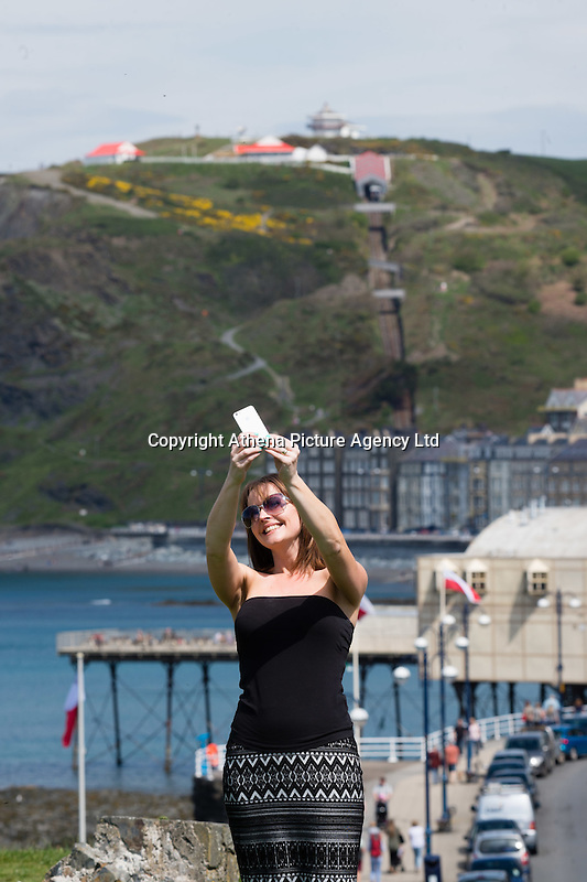 Aberystwyth Wales Uk, Sunday 08 May 2016<br /> Pictured: Hayley Reeves (34) from Oswestry, on a day trip to the seaside, takes a selfie with the promenade and town in the background<br /> UK Weather : As temperatures reach the upper 20's centigrade in parts of Britain, people enjoy the warm May sunshine in Aberystwyth on the Cardigan Bay coast in West Wales.