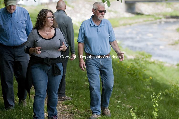 TORRINGTON, CT, 20  MAY 15 -  Rista Malanca, left, Torrington's zoning and wetlands officer walks along a path near the Naugatuck River that eventually could be a paved trail giving senior citizens a walking trail near the Sullivan Senior Center in Torrington. It will be a part of the Naugatuck River Greenway that eventually will stretch 44 miles from Derby to Torrington. She is with Tom Ross, right, and Mark Linehan, left, of the Torrington Trails Network.  Alec Johnson/ Republican-American