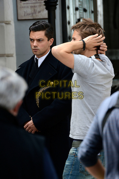 Dominic Cooper<br /> Filming on the set of 'Fleming' where Dominic Cooper stars as Ian Fleming, Central London, England.<br /> 29th June 2013<br /> cast crew tv mini series half length black coat<br /> CAP/IA<br /> &copy;Ian Allis/Capital Pictures