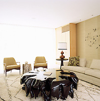 A pair of 1940s French armchairs and a curved sofa by Edward Wormley surround a coffee table by Shamir Shah in the living room