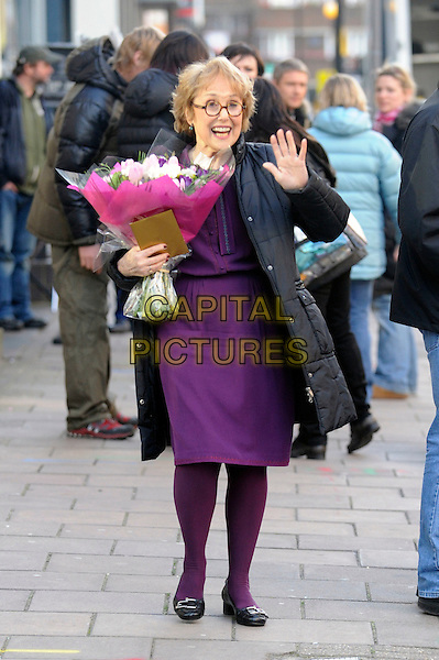 "UNA STUBBS  .Filming on the set of ""Sherlock"", Warren Street, London, England..April 11th, 2010.**EXCLUSIVE ALL ROUNDER**.full length purple tights black puffa jacket flowers bouquet hand palm waving .CAP/IA.©Ian Allis/Capital Pictures."
