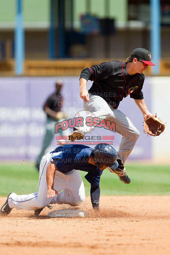 Austin Elkins (6) of the Quad Cities River Bandits loses his grip on the baseball as Devon Travis (6) of the West Michigan Whitecaps slides into second base to break up a double play at Fifth Third Ballpark on May 5, 2013 in Comstock Park, Michigan.  The River Bandits defeated the Whitecaps 5-4.  (Brian Westerholt/Four Seam Images)