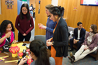 Virak Uy (second from right) speaks with Pam Flaherty (right), Dean of Students and Senior Stdent Affairs Officer, as people gather for a Lunar New Year celebration at Middlesex Community College's Asian American Connections Center on Thurs., Feb. 15, 2018. The Asian American Connections Center was established at the school using a federal grant in 2016 and serves as a focal point for the Asian community at the school, predominantly Cambodian, to gather, socialize, study, and otherwise take part in student life.  Uy is the Director of Asian American Student Advancement Program at Middlesex Community College and helped to establish the Asian American Connections Center