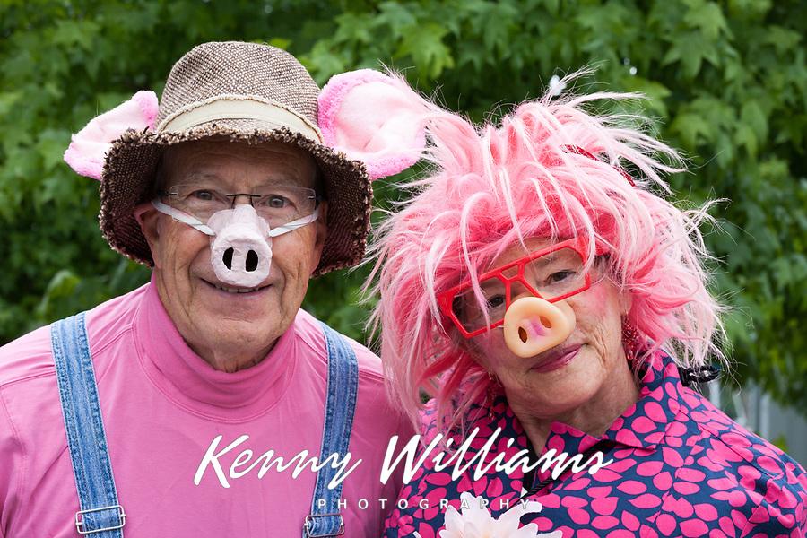 Senior man & woman having fun wearing pig noses, Fremont Solstice Parade & Festival, Seattle, Washington, USA.