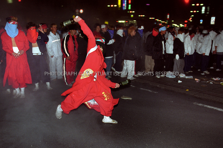 11/18/1999--Hiroshima, Japan..A  bosozoku gang member throws bottles at police during night of rioting on the streets of Hiroshima. Such gangs have been common in Japan for many years and are considered stepping stones to join yakuza gangs and 'uyoku' or rightwing nationalsist groups....All photographs ©2003 Stuart Isett.All rights reserved.This image may not be reproduced without expressed written permission from Stuart Isett.