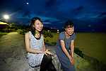 Shiori Abe (R) and Kaori Minenishi, volunteers from Hokkaido who are participating in a coral reef restoration project, enjoy the scenery from the municipal beach at Onna Village, Okinawa Prefecture, Japan, on Saturday, June 23, 2012. Photographer: Robert Gilhooly