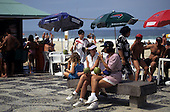Ipanema Beach, Rio de Janeiro, Brazil. Two women drinking from fresh coconuts at a beach-side bar.