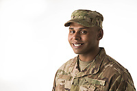 Studio portrait of African American Army soldier Ralph looking at camera with white background