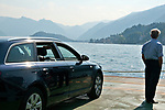 A man looks at the view while standing next to his car on the car ferry from Bellagio to Cadenabbia; Lake Como, Italy