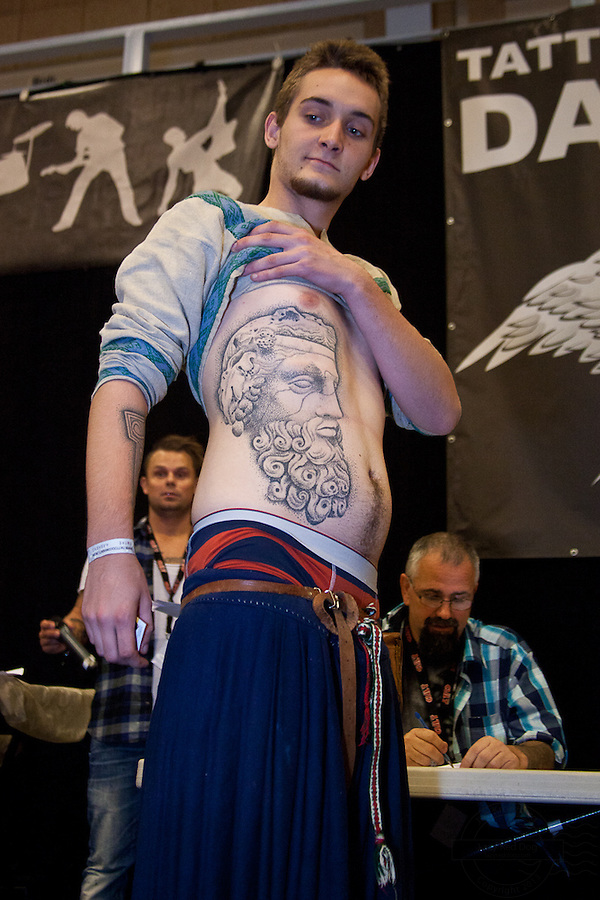 Tattoo Convention in Kolding 2011. Arranged by BodyMod.dk<br /> Young man in traditional clothing with face tattooed on stomach i black and grey.